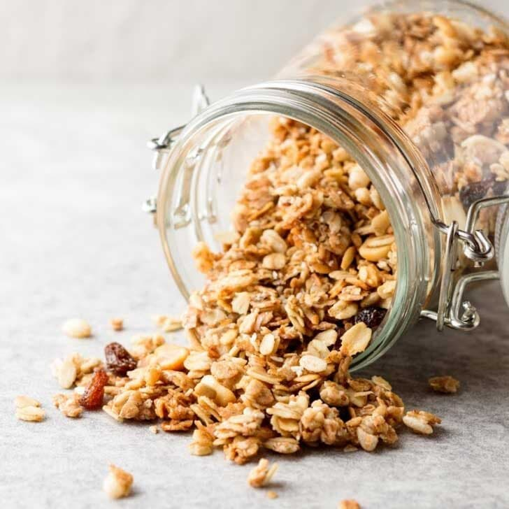 Homemade granola spilling out of a tipped glass jar.