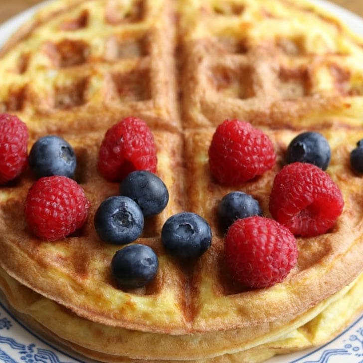 "Low-carb cheesy waffle (""chaffle"") with blueberries and raspberries on top."