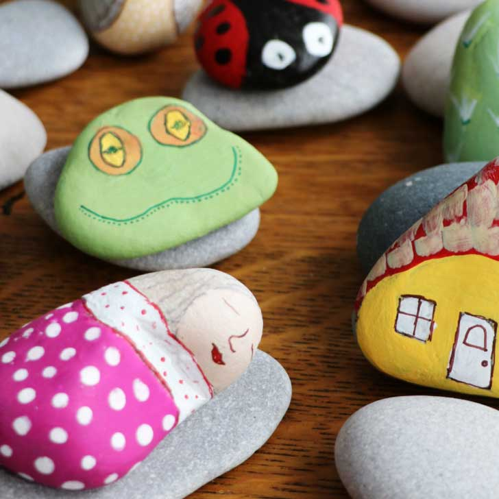 Handpainted stones featuring a sleeping woman, frog, ladybug, and house.