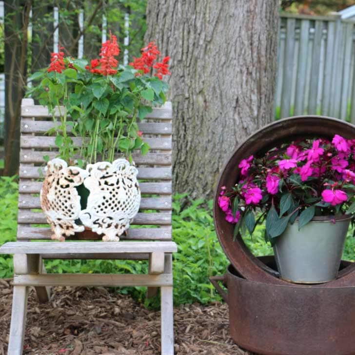 Simple garden art ideas including using a recycled wood chair to hold a flower planter.