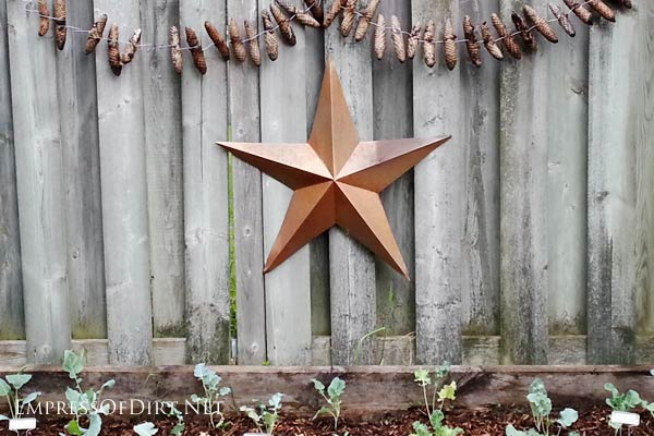 Decorative star and chain of pinecones on garden fence.