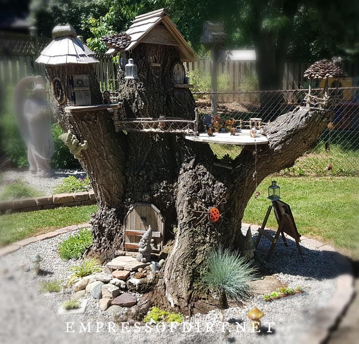 Tree stump in garden made into a doll-size playhouse.