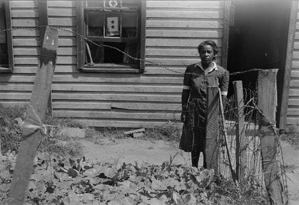 Woman standing by front yard vegetable garden
